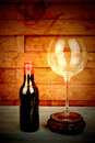 Big wine glass and bottle on a wooden background Stock Photography