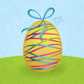 Big yellow easter egg with colorful ribbons Stock Image