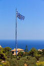 Biggest greek flag view on the mast of the in the world at keri on the island zakynthos greece with strong winds a smaller is Stock Photography