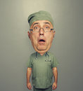 Bighead amazed doctor in glasses and uniform over grey background Royalty Free Stock Photo