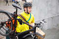 Bike courier delivery man in protective gear with bicycle and package walking up steps Royalty Free Stock Images