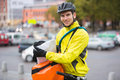 Bike courier portrait of young male cyclist putting package in bag on street Stock Photo
