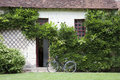 Bike near the entrance in a traditional house, France Stock Photo