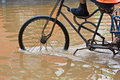 Bike riding through flooded streets Royalty Free Stock Image