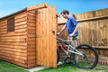 Bike storage a may pushing his into his shed for Stock Image