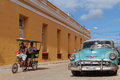 Bike taxi and old american car in Trinidad Royalty Free Stock Photo