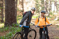 Biker couple standing with mountain bike on dirt track Royalty Free Stock Photo
