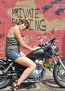 Biker gal relaxing on her motorcycle outside Royalty Free Stock Photography