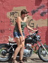 Biker gal relaxing on her motorcycle outside Stock Photography