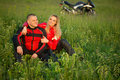 Biker girl and man sitting on the grass near a Royalty Free Stock Photo