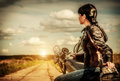 Biker girl on a motorcycle in leather jacket looking at the sunset Royalty Free Stock Photography