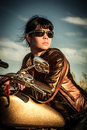 Biker girl on a motorcycle in leather jacket looking at the sunset Royalty Free Stock Image