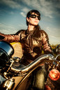 Biker girl on a motorcycle in leather jacket looking at the sunset Stock Photo