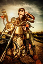 Biker girl on a motorcycle in leather jacket looking at the sunset Royalty Free Stock Photo