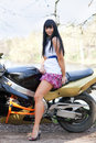 Biker girl on a motorcycle standing beside beautiful woman standing next to outdoors in short skirt and sportbike Stock Image