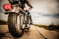 Biker girl riding on a motorcycle bottom view of the legs in leather boots focus the rear wheel Stock Photos