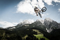 Biker jumps high with his bike rotates arround in the air Stock Images