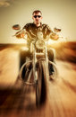Biker in a leather jacket riding a motorcycle on the road Stock Photo