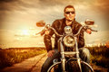 Biker on a motorcycle man wearing leather jacket and sunglasses sitting his looking at the sunset Royalty Free Stock Photos