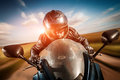 Biker racing on the road in helmet and leather jacket Stock Photos