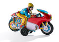 Biker retro tin toy with a in goggles crouched down on a colorful motorcycle mounted on wheels on a white background Royalty Free Stock Photos