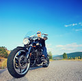 Biker riding a customized motorcycle on an open road Stock Photo
