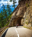 Biker riding into mountainous tunnel extreme lifestyle active holidays race in alps austria europe moto sport travel and tourism Stock Photo