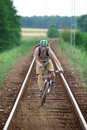 Biker riding on railway track Stock Photos