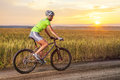 Biker riding rural road against sunset Royalty Free Stock Photo