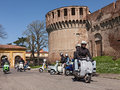 Bikers riding a vintage italian scooters lambretta and vespa with the castle on background at motorcycle rally iv vespa in fiore Stock Image