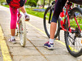 Bikes bicyclist girl. Children feet and bicycle wheel. Low section. Royalty Free Stock Photo