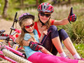 Bikes cycling family. Happy mother and daughter are sitting on road near bicycles. Royalty Free Stock Photo
