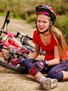 Bikes cycling girl wearing helmet fell off bike. Royalty Free Stock Photo
