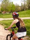 Bikes cycling girl wearing helmet ride on road into park. Royalty Free Stock Photo