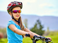Bikes cycling girl wearing helmet rides bicycle. Royalty Free Stock Photo