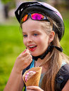 Bikes cycling girls with rucksack cycling eating ice cream cone in summer park bicyclist girl portrait of child wearing bicycle Royalty Free Stock Images