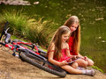 Bikes cycling kids. Girl recreation near bicycle into park. Royalty Free Stock Photo