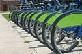 Bikes a row of identical parked along a sidewalk Royalty Free Stock Photo