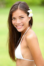 Bikini girl wearing hawaiian flower in hair young woman smiling fresh and healthy gorgeous mixed race asian caucasian female model Stock Photography