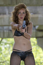 Bikini gun woman clad in gangster style aiming with a handgun outdoor Royalty Free Stock Images