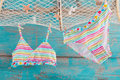 Bikini hanging from the fishing net on turqoise wooden backgroun background Royalty Free Stock Photography