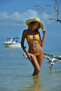 Bikini model in straw hat posing sexy in front of camera at tropical beach location with drift wood tree and fishing boat on Stock Photography
