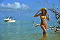 Bikini model in straw hat posing sexy in front of camera at tropical beach location with drift wood tree and fishing boat on Royalty Free Stock Images