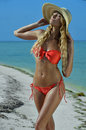 Bikini model in straw hat posing sexy at tropical beach location Royalty Free Stock Photos