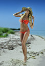 Bikini model in straw hat posing sexy at tropical beach location Stock Photo