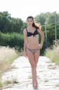 Bikini woman among in high dry grass with ponytail hair standing tip toe wearing looking at the camera full length and Stock Photo