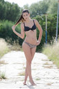 Bikini woman among in high dry grass with ponytail hair standing tip toe wearing looking at the camera full length and Stock Image