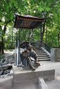 Bila Tserkva, Ukraine, 19.09.2009 a statue of a seated Japanese elder near a Japanese-style gazebo called Tea house in the park in Royalty Free Stock Photo
