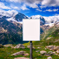 Billboard for advertising mounted on a meadow among the mountain blank mountains with snow capped peaks flower in alpine Stock Photo
