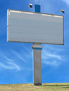 Billboard advertising panel with empty space and light projector projectors over blue sky background Stock Images